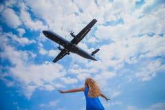 Χαριτωμένος λίγο κορίτσι παιδιών που κοιτάζει στον ουρανό και το πετώντας αεροπλάνο άμεσα επάνω από την Στοκ εικόνα με δικαίωμα ελεύθερης χρήσης