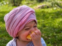 Χαριτωμένος λίγο μικρό παιδί κοριτσάκι που τρώει τα πορτοκαλιά φρούτα Στοκ φωτογραφίες με δικαίωμα ελεύθερης χρήσης