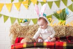 Χαριτωμένος λίγο μωρό που φορά τα αυτιά λαγουδάκι την ημέρα και το κτύπημα ρ Πάσχας Στοκ Εικόνες