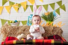 Χαριτωμένος λίγο μωρό που φορά τα αυτιά λαγουδάκι την ημέρα Πάσχας Στοκ Εικόνα