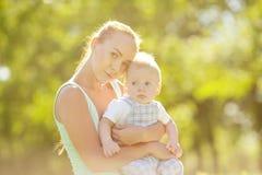 Χαριτωμένος λίγο μωρό στο θερινό πάρκο με τη μητέρα στη χλόη. Swee Στοκ Φωτογραφίες