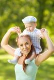 Χαριτωμένος λίγο μωρό στο θερινό πάρκο με τη μητέρα στη χλόη. Swee Στοκ Εικόνα