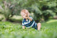 Χαριτωμένος λίγο μωρό στο θερινό πάρκο στη χλόη Γλυκό μωρό υπαίθριο Στοκ Φωτογραφία