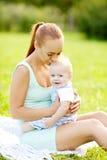 Χαριτωμένος λίγο μωρό στο πάρκο με τη μητέρα στη χλόη. Γλυκό bab Στοκ εικόνα με δικαίωμα ελεύθερης χρήσης