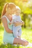 Χαριτωμένος λίγο μωρό στο πάρκο με τη μητέρα στη χλόη. Γλυκό bab Στοκ Εικόνες