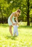 Χαριτωμένος λίγο μωρό στο πάρκο με τη μητέρα στη χλόη. Γλυκό bab Στοκ φωτογραφία με δικαίωμα ελεύθερης χρήσης