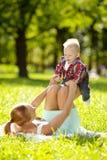 Χαριτωμένος λίγο μωρό στο πάρκο με τη μητέρα στη χλόη. Γλυκό bab Στοκ Φωτογραφία