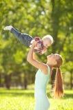 Χαριτωμένος λίγο μωρό στο πάρκο με τη μητέρα στη χλόη Στοκ Φωτογραφίες