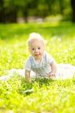 Χαριτωμένος λίγο μωρό στο πάρκο στη χλόη. Γλυκό μωρό υπαίθρια. Στοκ Φωτογραφία