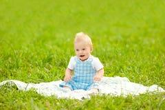 Χαριτωμένος λίγο μωρό στο πάρκο στη χλόη. Γλυκό μωρό υπαίθρια. Στοκ Εικόνες