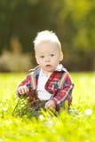 Χαριτωμένος λίγο μωρό στο πάρκο στη χλόη. Γλυκό μωρό υπαίθρια. Στοκ φωτογραφία με δικαίωμα ελεύθερης χρήσης