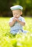 Χαριτωμένος λίγο μωρό στο πάρκο στη χλόη. Γλυκό μωρό υπαίθρια. Στοκ Εικόνα