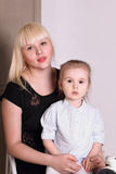 Χαριτωμένος λίγο ξανθό κορίτσι στη ριγωτή συνεδρίαση πουκάμισων στην περιτύλιξη της μητέρας Στοκ Φωτογραφία