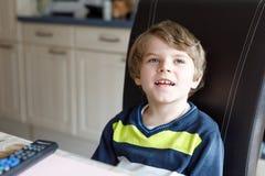 Χαριτωμένος λίγο ξανθό προσχολικό αγόρι παιδιών που προσέχει τη TV Στοκ Φωτογραφία