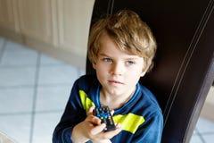 Χαριτωμένος λίγο ξανθό προσχολικό αγόρι παιδιών που προσέχει τη TV Στοκ Εικόνες