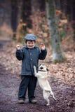 Χαριτωμένος λίγο παιδί, που παίζει με λίγο σκυλί κατοικίδιων ζώων στο δάσος Στοκ Φωτογραφία