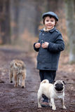 Χαριτωμένος λίγο παιδί, που παίζει με λίγο σκυλί κατοικίδιων ζώων στο δάσος Στοκ Φωτογραφίες