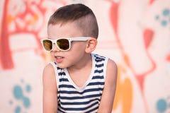 Χαριτωμένος λίγο παιδί που φορά το άσπρο πουκάμισο γυαλιών ηλίου και λωρίδων ναυτικών Στοκ Φωτογραφία