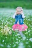 Χαριτωμένος λίγο χαμογελώντας κοριτσάκι στο chamomile τομέα λίγο ξανθό παιδί με το στεφάνι στο κεφάλι στα chamomiles που φορούν τ Στοκ Φωτογραφίες