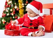 Χαριτωμένος λίγο δώρο ανοίγματος santa μωρών για τα Χριστούγεννα Στοκ Εικόνες