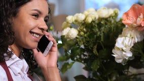 Χαριτωμένος ανθοκόμος που χρησιμοποιεί το τηλέφωνο για τη λήψη των διαταγών στο κατάστημα απόθεμα βίντεο