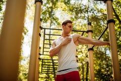 Χαριτωμένος αρσενικός αθλητής που θερμαίνει πριν από την οδό workout στοκ φωτογραφία