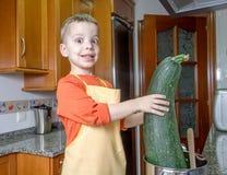 Χαριτωμένος αρχιμάγειρας παιδιών που μαγειρεύει τα μεγάλα κολοκύθια σε ένα δοχείο Στοκ εικόνες με δικαίωμα ελεύθερης χρήσης