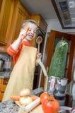 Χαριτωμένος αρχιμάγειρας παιδιών που μαγειρεύει τα μεγάλα κολοκύθια σε ένα δοχείο Στοκ Φωτογραφίες