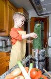 Χαριτωμένος αρχιμάγειρας παιδιών που μαγειρεύει τα μεγάλα κολοκύθια σε ένα δοχείο Στοκ Εικόνες