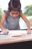 Χαριτωμένος Ασιάτης λίγο κορίτσι παιδιών προετοιμάζει μια ζύμη για τα μπισκότα ψησίματος Στοκ Εικόνες