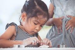 Χαριτωμένος Ασιάτης λίγο κορίτσι παιδιών προετοιμάζει μια ζύμη για τα μπισκότα ψησίματος Στοκ φωτογραφίες με δικαίωμα ελεύθερης χρήσης