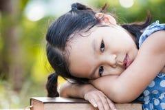 Χαριτωμένος Ασιάτης λίγο κορίτσι παιδιών με το τρυπημένο συναίσθημα για να διαβάσει ένα βιβλίο Στοκ Εικόνες