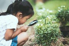 Χαριτωμένος Ασιάτης λίγο κορίτσι παιδιών που κοιτάζει μέσω μιας ενίσχυσης - γυαλί Στοκ Εικόνες