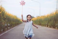 Χαριτωμένος Ασιάτης λίγο κορίτσι παιδιών που παίζει με τον ανεμοστρόβιλο Στοκ εικόνα με δικαίωμα ελεύθερης χρήσης