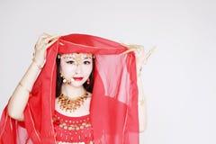 Χαριτωμένος ασιατικός κινεζικός χορευτής κοιλιών που καλύπτεται στο πέπλο μεταξιού στο άσπρο υπόβαθρο Στοκ Εικόνες