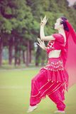 Χαριτωμένος ασιατικός κινεζικός χορευτής κοιλιών που χορεύει στη χλόη Στοκ Εικόνα