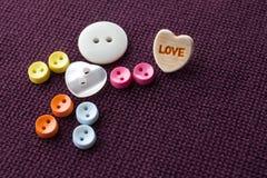Χαριτωμένος αστείος χαρακτήρας με την καρδιά αγάπης Ζωηρόχρωμος ράβοντας ήρωας κουμπιών στο ιώδες υφαντικό υπόβαθρο ανασκόπησης η Στοκ φωτογραφία με δικαίωμα ελεύθερης χρήσης
