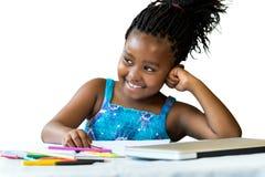 Χαριτωμένος αφρικανικός σπουδαστής στο γραφείο με τα μολύβια χρώματος Στοκ Εικόνες