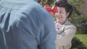 Χαριτωμένος εγγονός που επισκέπτεται τη γιαγιά του, που φέρνει την ανθοδέσμη τουλιπών της Το γενειοφόρο άτομο που αγκαλιάζει τη γ φιλμ μικρού μήκους