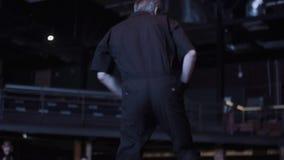 Χαριτωμένος ενεργός τύπος στα σκοτεινά μαύρα ενδύματα που δυναμικά στη σκηνή φιλμ μικρού μήκους