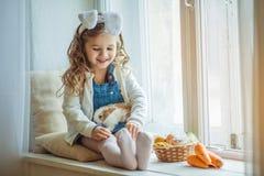 Χαριτωμένος ευτυχής λίγο κορίτσι παιδιών φορά τα αυτιά λαγουδάκι την ημέρα Πάσχας που κρατά το φίλο της λίγο γούνινο κουνέλι Στοκ Φωτογραφίες