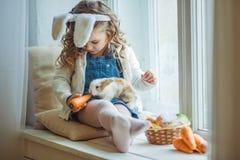Χαριτωμένος ευτυχής λίγο κορίτσι παιδιών φορά τα αυτιά λαγουδάκι την ημέρα Πάσχας που κρατά το φίλο της λίγο κουνέλι Στοκ Εικόνες