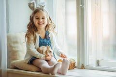 Χαριτωμένος ευτυχής λίγο κορίτσι παιδιών φορά τα αυτιά λαγουδάκι την ημέρα Πάσχας που κρατά λίγο κουνέλι Στοκ εικόνα με δικαίωμα ελεύθερης χρήσης