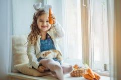 Χαριτωμένος ευτυχής λίγο κορίτσι παιδιών φορά τα αυτιά λαγουδάκι την ημέρα Πάσχας που κρατά το φίλο της λίγο κουνέλι και καρότα Στοκ φωτογραφίες με δικαίωμα ελεύθερης χρήσης