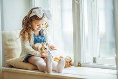 Χαριτωμένος ευτυχής λίγο κορίτσι παιδιών φορά τα αυτιά λαγουδάκι την ημέρα Πάσχας που κρατά λίγο κουνέλι Στοκ εικόνες με δικαίωμα ελεύθερης χρήσης