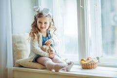 Χαριτωμένος ευτυχής λίγο κορίτσι παιδιών φορά τα αυτιά λαγουδάκι την ημέρα Πάσχας που κρατά λίγο κουνέλι Στοκ φωτογραφία με δικαίωμα ελεύθερης χρήσης