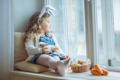 Χαριτωμένος ευτυχής λίγο κορίτσι παιδιών φορά τα αυτιά λαγουδάκι την ημέρα Πάσχας που κρατά το φίλο της λίγο ζωηρόχρωμο κουνέλι Στοκ φωτογραφία με δικαίωμα ελεύθερης χρήσης