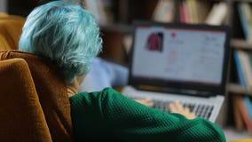 Χαριτωμένος θηλυκός πελάτης που ψωνίζει on-line με το lap-top απόθεμα βίντεο