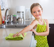 Χαριτωμένος καθαρισμός μικρών κοριτσιών στην κουζίνα Στοκ εικόνες με δικαίωμα ελεύθερης χρήσης