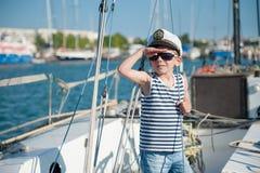 Χαριτωμένος καπετάνιος μικρών παιδιών που φορά τον καπετάνιο ΚΑΠ και γυαλιά ηλίου στη βάρκα πολυτέλειας Στοκ Φωτογραφίες